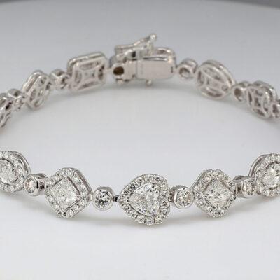 Halo Designer Tennis Bracelet in 18K WG w/ Round diamonds around assorted fancy shape diamonds centers & Round diamonds. D9.78ct.t.w.